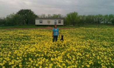 My Ti Anita standing in her front yard of wild flowers.
